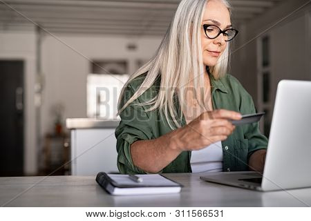 Mature woman using credit card making online payment at home. Successful old woman doing online shopping using laptop. Closeup of retired lady holding debit card for internet banking account.
