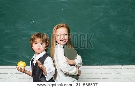 Apple And Books - School Concept. Girl And Boy With Happy Face Expression Near Desk With School Supp