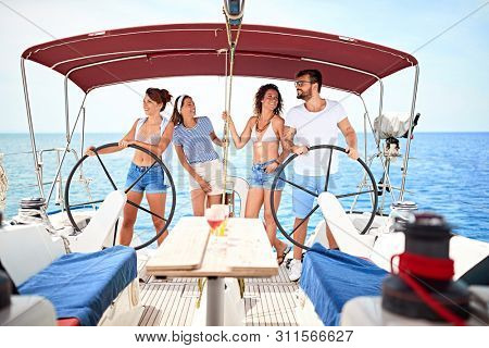 Smiling friends sailing on yacht .- Summer holidays