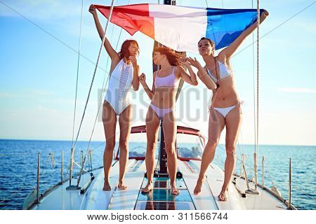 Smiling woman on the yacht in flag having party on vacation