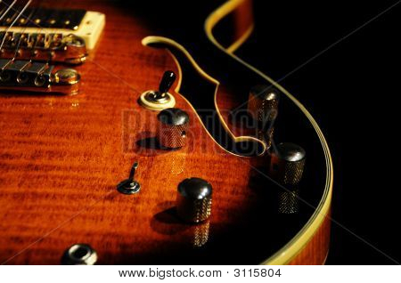 Closeup of a hollowbody guitar with a sunburst finish. F-Hole and volume nobs pickups and string are visible. Shallow Depth Of Field. poster