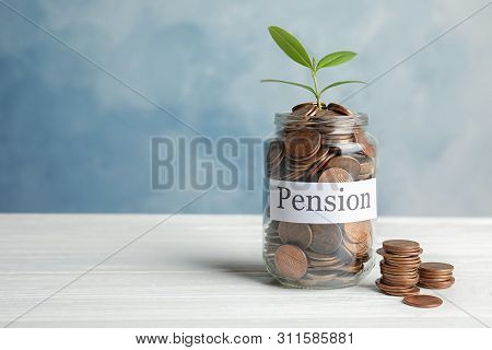 Glass Jar With Label Pension, Coins And Green Plant On White Table. Space For Text