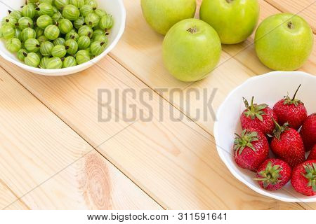 Fresh Fruits And Berries On A Light Wooden Table With Copy Space. Green Apples, Gooseberry And Red S
