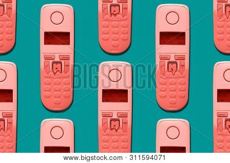 Pattern Image Of Coral Color Dect Phones Turning Into A Toy Phones On Blue Background. The Concept O