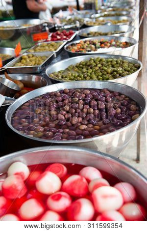 Different pickled olives in brine in outdoor market