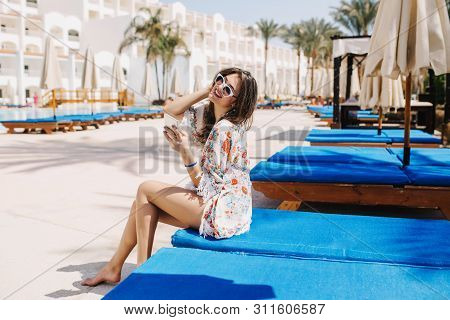 Fascinating Barefooted Dark-haired Girl Having Fun Outside, Resting On Chaise-longue Near The Hotel.