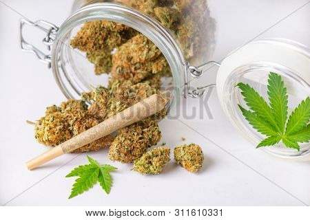 Detail of cannabis buds and joint on clear glass jar isolated on white - medical marijuana dispensary concept