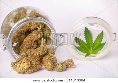 Detail of cannabis buds on clear glass jar isolated on white - medical marijuana dispensary concept