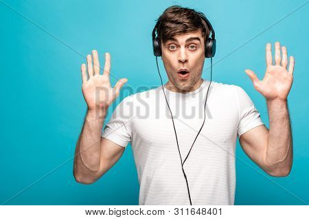 Discouraged Young Man Showing Give Up Gesture While Listening Music In Headphones On Blue Background