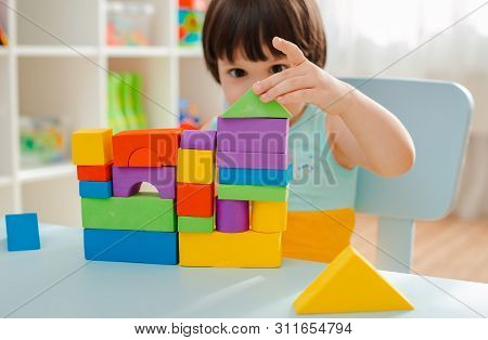 Little Girl Collects A Wooden Unpainted Pyramid. Safe Natural Wooden Childrens Toys. Wooden Blanks F