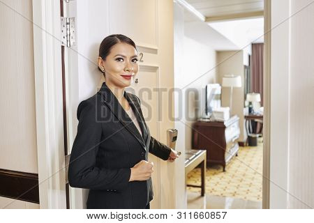 Portrait Of Beautiful Asian Manager Of The Hotel In Black Suit Standing Near The Door Opening It And
