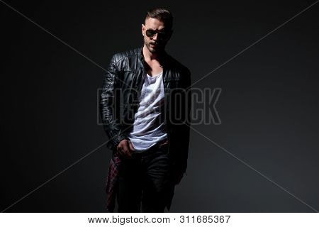 Motivated punk man stepping forward while wearing a black leather jacket and sunglasses on black studio background