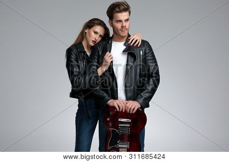 Unsure young man licking his lips while his girlfriend is embracing him, both wearing black leather jackets and jeans, standing on gray studio background