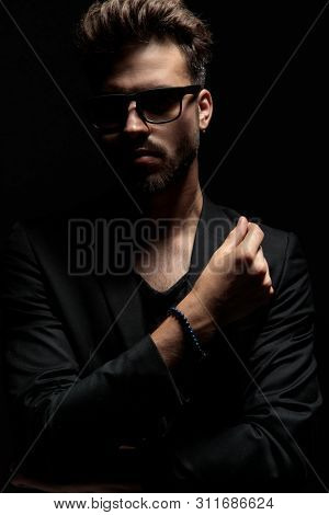 Tough dramatic man holding his hand crossed and looking forward while wearing a black jacket and sunglasses, standing on black studio background