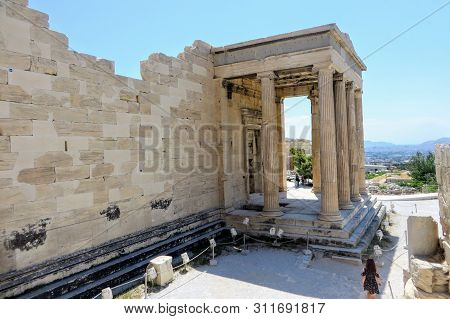 A young woman walking around the Acropolis by herself admiring the glorious ancient Greek Old Temple of Athena atop the Acropolis, in Athens, Greece. poster