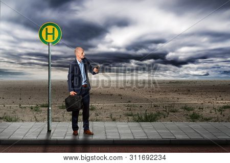 A Businessman Waits In Vain At A Bus Stop In The Middle Of Nowhere, Illustrating A Bad Step In His C