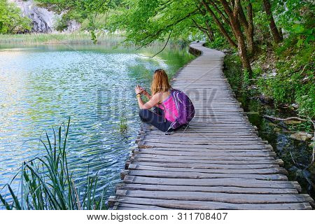 Woman Taking A Break And Meditating On A Wooden Boardwalk Bridge Near Turquoise Waters Of Plitvice L