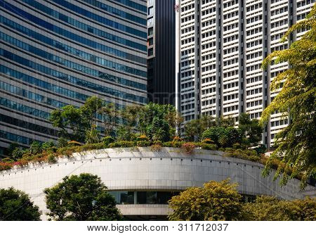 Modern Glass Buildings With Garden And Trees On Roof In Singapore