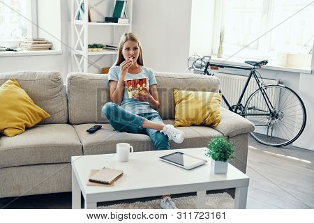 Beautiful Young Woman Eating Popcorn While Watching Tv On The Sofa At Home