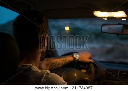 Young Man With Earrings Drives A Car At Night