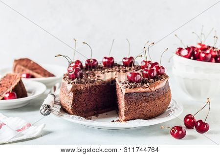 Sliced Chocolate Cake Decorated With Chocolate Shavings And Sweet Cherries, Copy Space For Your Text