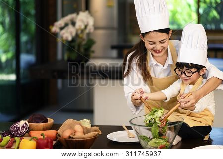 Happy Asian Family In The Kitchen.mother And Son Help To Make Vegetable Salad.mom Teaching Kid Boy C