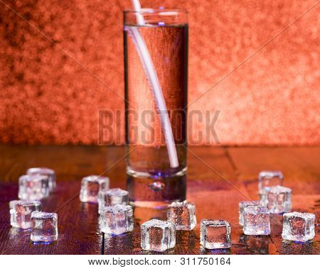 Melting Cubes Of Transparent Cold Ice And A Glass Of Soda With Cocktail Straw