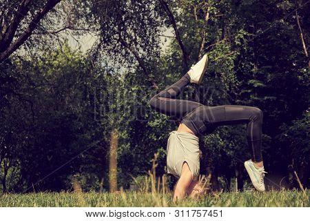 Beautiful Sporty Fit Yogi Woman Practices Yoga Handstand Asana Bhuja Vrischikasana - Scorpion Handst