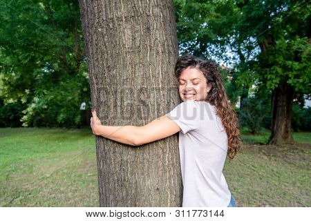 Tree Hugging, Beautiful Smiling Young Positive And Happy Environmentalist Girl Hugging The Big Tree