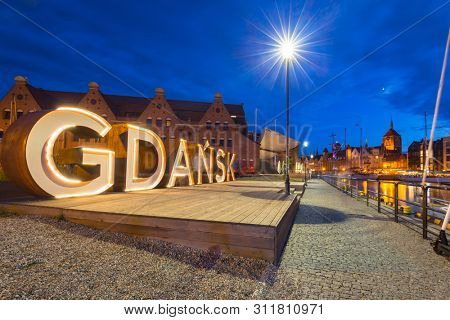 Gdansk, Poland - July 8, 2019: Beautiful architecture of Gdansk with an outdoor sign at dusk, Poland
