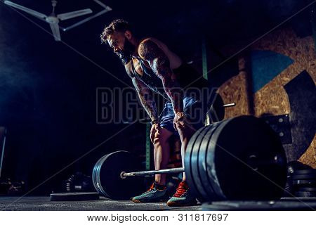Muscular Fitness Man Preparing To Deadlift A Barbell Over His Head In Modern Fitness Center. Functio