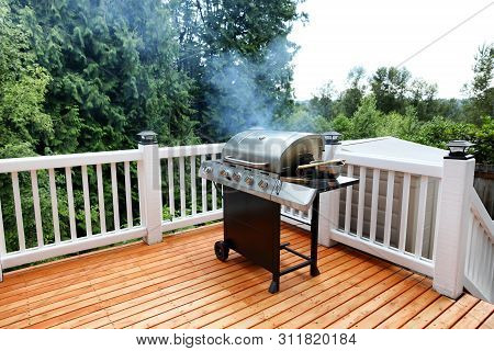 Barbecue Grill Cooking In Open Outdoor Deck During Summer Day