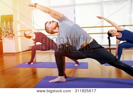 Fitness, Yoga And Healthy Lifestyle Concept - A Group Of People Who Do Exercises For Stretching And