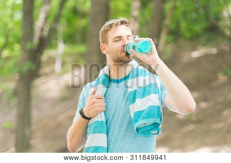 Water Is Indispensable For Human Health. Fit Athlete Having A Drink From Water Bottle During Trainin
