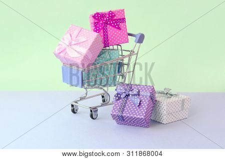 Small Gift Boxes Of Different Colors With Ribbons In Shopping Cart On A Violet And Blue Pastel Backg