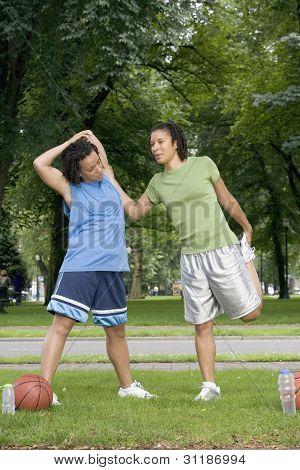 Two teenage girls stretching