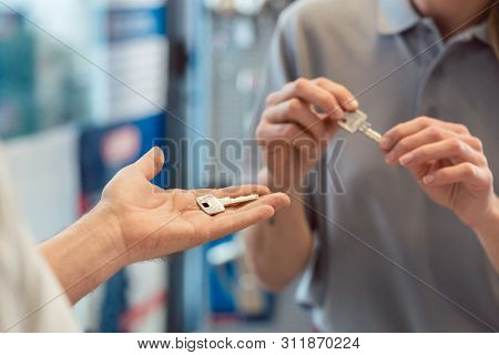 Woman asking locksmith to make a key copy, duplicate, close-up