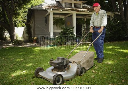 Portrait of elderly man mowing lawn