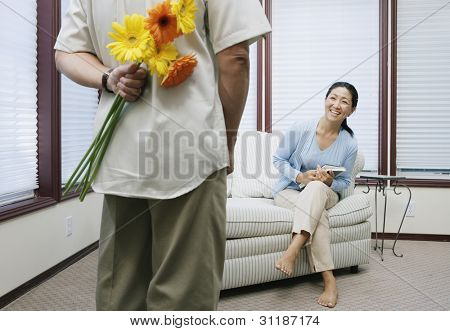 Man hiding flowers behind back for woman