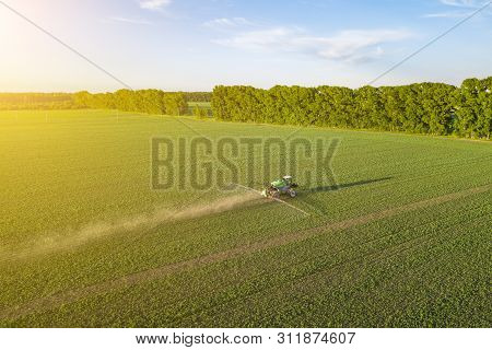 Aerial View Of A Farm Tractor In A Green Field During Spraying And Irrigation With Pesticides And To