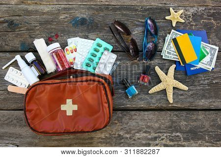 Summer Women's Beach Accessories For Your Sea Holiday And First Aid Kit On Old Wooden Background. Co