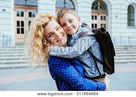 Meeting After School. Portrait Of Happy Blond Curly Caucasian Mother And Her Son Hugging, Laughing G