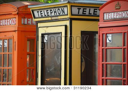 Three antique European telephone booths in a line.