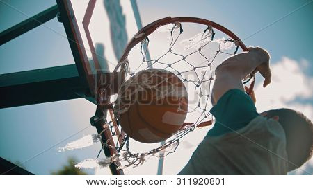 A Basketball Hoop - A Man Throwing The Ball And It Gets In The Target - Slam Dunk