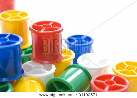 Colourful bobbins with shallow depth of field on a white background.