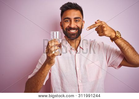 Young handsome indian man dinking glass of water over isolated pink background very happy pointing with hand and finger