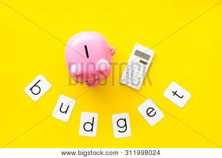 Moneybox in shape of pig, word budget and calculator on yellow background top view poster