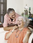 Affectionate senior man and woman at home on couch smiling poster