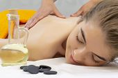 Spa hot stone massage. Attractive beautiful girl lying on massage bed in spa salon. Spa aroma therapy and beauty treatments concept poster