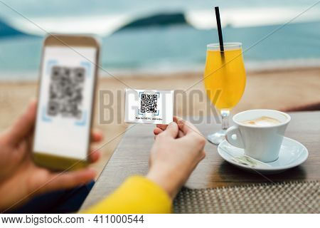 Women's Hands Are Using The Phone To Scan The Qr Code To Select Menu. Scan To Get Discounts Or Pay F